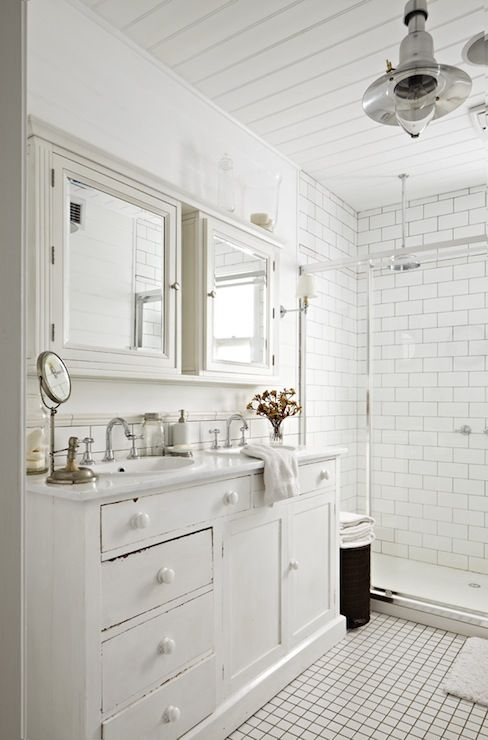 a lovely vintage whitewashed vanity with two oval sinks and vintage faucets, with matching whitewashed mirror cabinets over the vanity