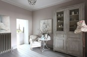 a whitewashed storage cupboard is a statement piece in this vintage and chic whitewashed room