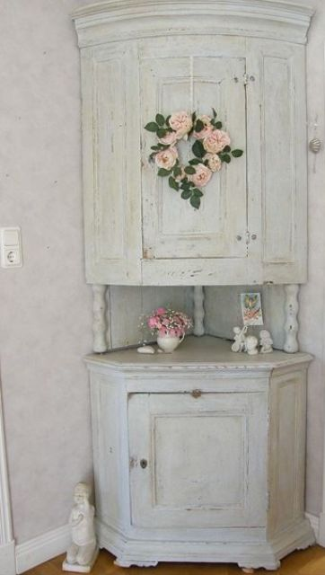 a vintage whitewashed corner cabinet of two parts connected with each other and with pink blooms is a lovely idea