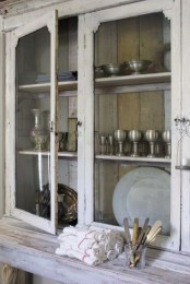 a vintage whitewashed cabinet with a colorful planked back and with glass doors is a very chic and cool idea