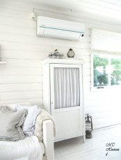 a stylish and small whitewashed cabinet with a glass door but with curtains is a cool idea for a Scandinavian interior
