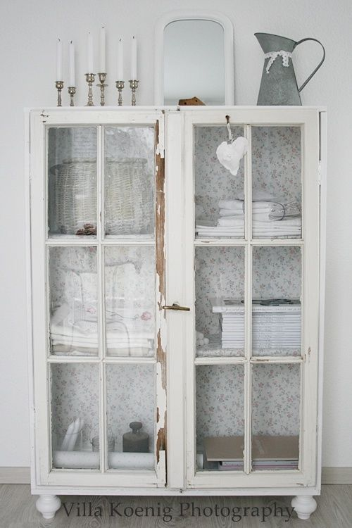 a shabby chic whitewashed cabinet with glass doors can display and store anything you want and it looks lightweight