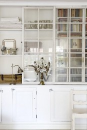 an oversized whitewashed storage cabinet with glass sliding doors and closed storage cabinet is a lovely idea for any space