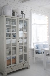 a pretty whitewashed glass cupboard like this one will give you storage and display at the same time and it looks very airy and lightweight