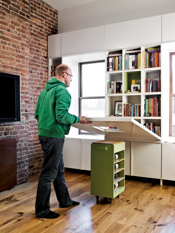 a desk, kitchen island or dining table can be folded to cover the shelves or unfolded to use it