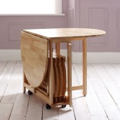 a simple round folding dining table and some folding chairs hidden inside is a great option for a small indoor or outdoor space