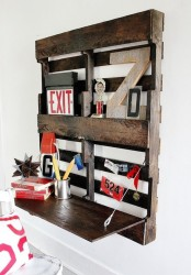 a dark stained pallet storage unit and a foldable desk with various stuff is a simple DIY for your space