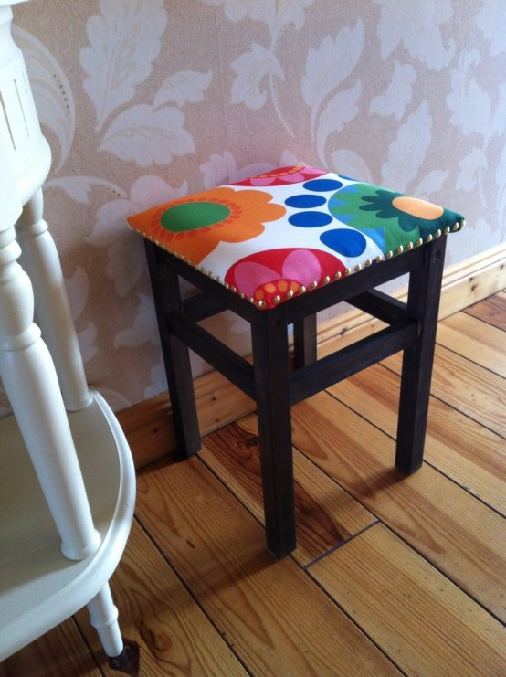 an IKEA Oddvar stool painted dark and upholstered with bright fabric and with decorative nail trim