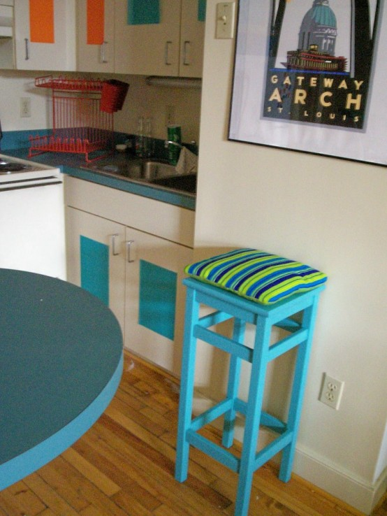 an IKEA Oddvar stool with added height, painted turquoise and with bright upholstery