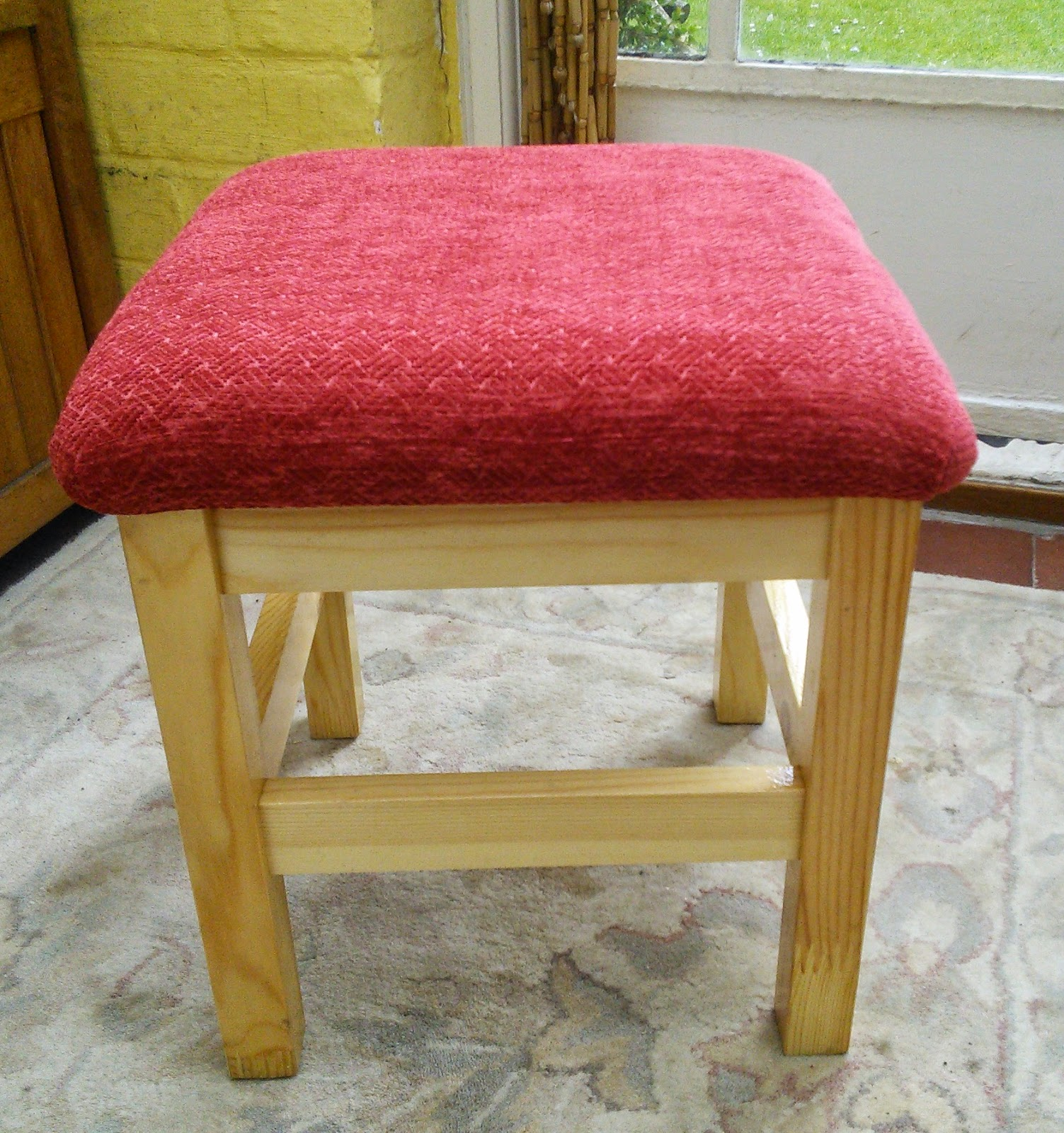 a neutral IKEA Oddvar stool refreshed with bright red upholstery for a touch of color in your space
