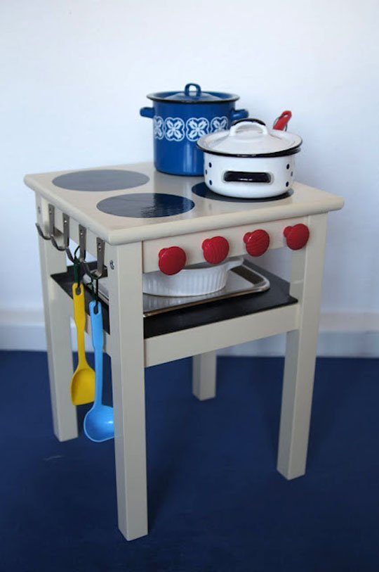 a bold kids' kitchen made of an IKEA Oddvar stool with hooks, knobs and trays