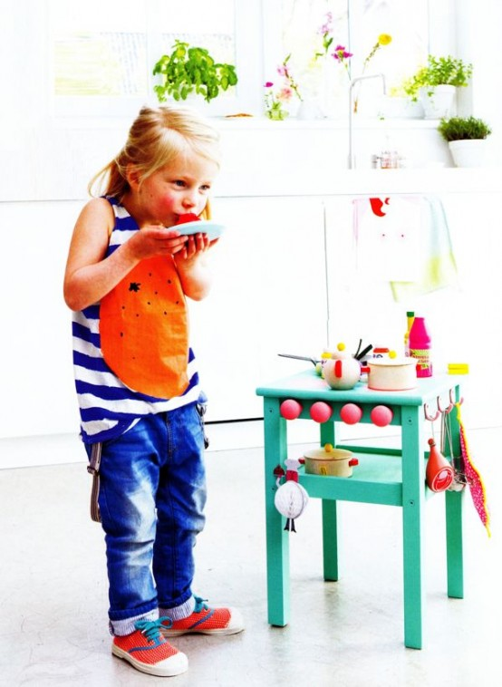 a bright kids' kitchen made of an IKEA Oddvar stool painted emerald and redone with hooks and other accessories
