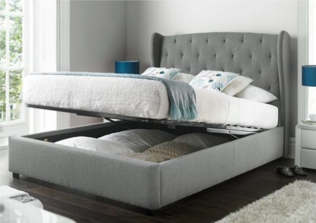a grey upholstered bed that can be raised to place some things inside it is a cool piece to rock