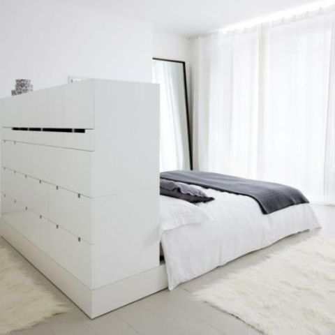 a large white minimalist bed with a storage headboard with lots of drawers that doubles as a space divider is brilliant