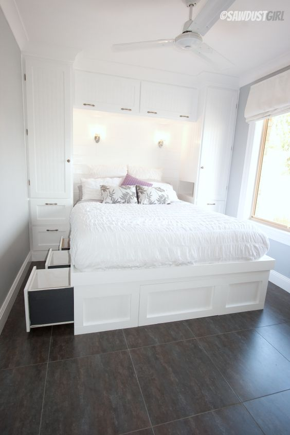 a built-in white bed with storage drawers in the sides of the bed is a cool solution and storage units on both sides of it will add storage space
