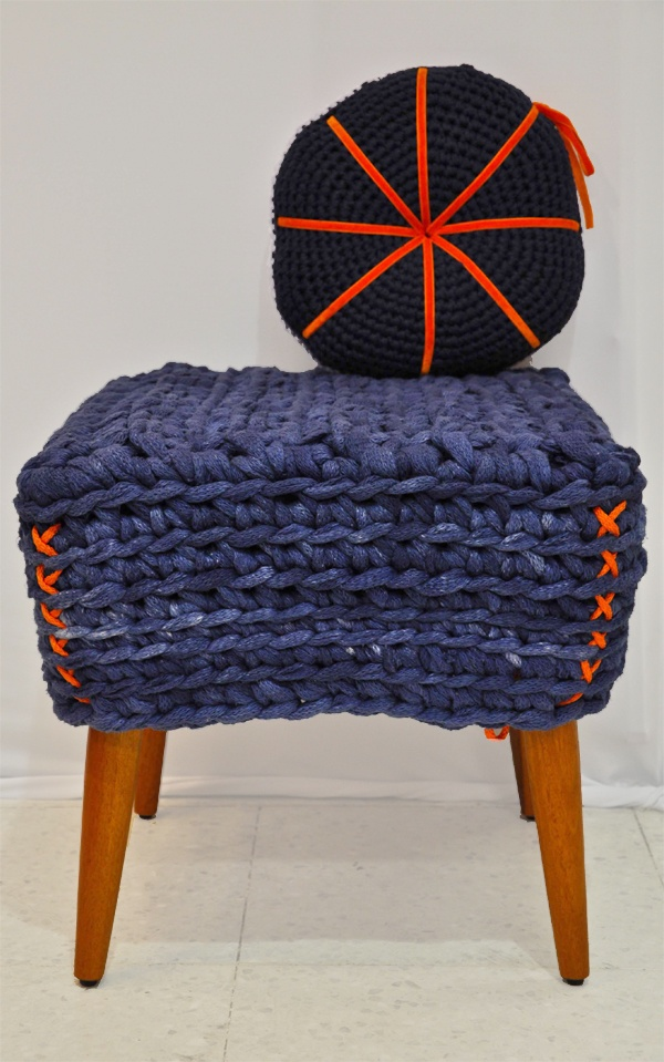 a navy crocheted stool with a colorful pillow will be a cool solution for your entryway, living room or sunroom