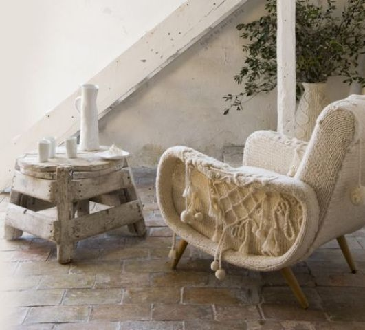 a mid century modern chair with a white crochet cover and tassels is a lovely idea that will cozy you up