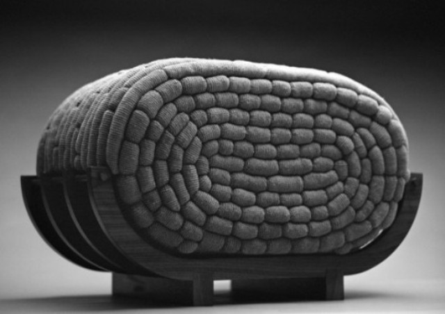 a creative curved seat with a crocheted filled is a very catchy and non typical furniture piece