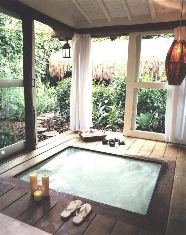 a jacuzzi with a deck around it, some lamps and candles plus sliding doors that allow making the spa indoor or outdoor