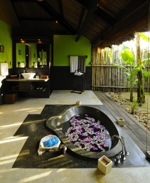 a sunken stone bathtub with floating flowers to get maximum of the bamboo garden view