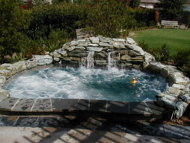 an outdoor jacuzzi with a waterfall clad with stone will be loved by everyone