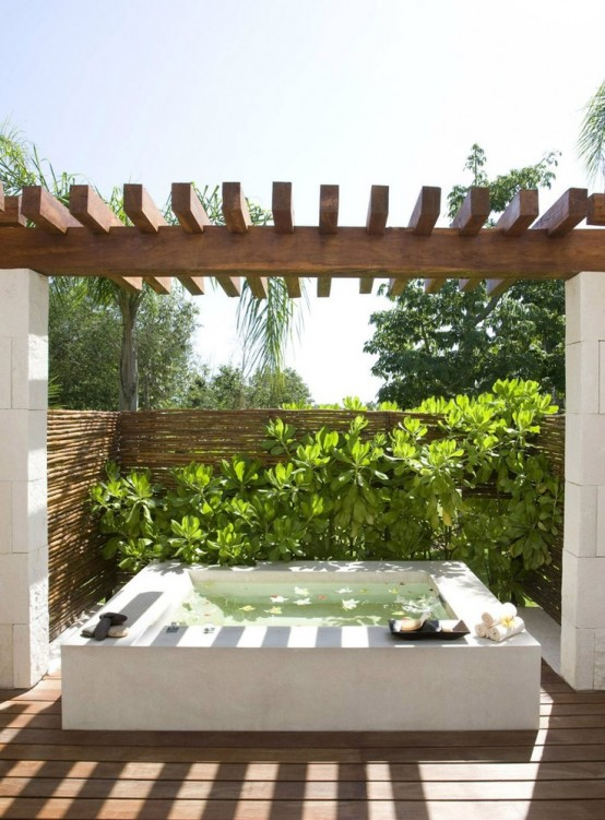 an outdoor bathtub of stone with walls for privacy and lush greenery to make it feel outdoorsy