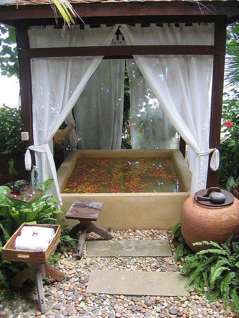 an outdoor stone bathtub with a cover over it and some curtains for privacy, potted greenery refresh the space