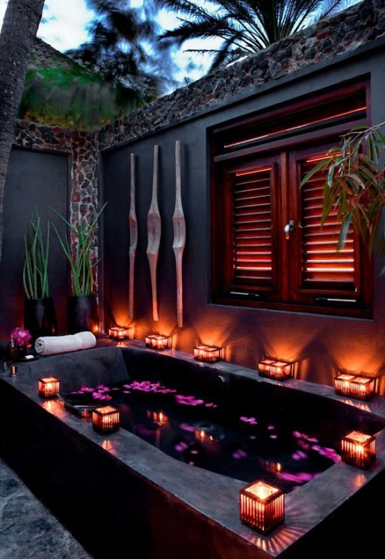 an outdoor stone bathtub with candle lanterns on the edges and tall walls to keep privacy