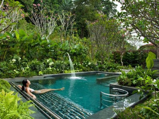 a small outdoor pool with a waterfall and greenery growing around create your personal oasis for relaxation