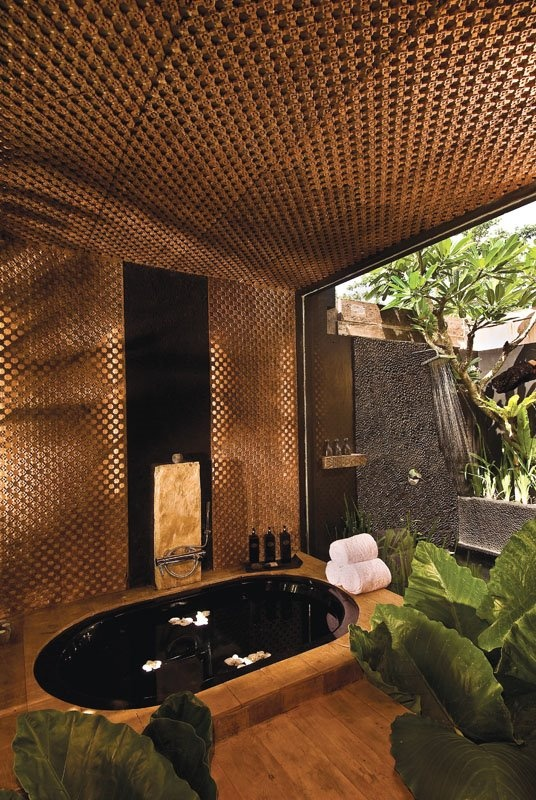a sunken bathtub with a wooden deck, an outdoor shower next to it and a roof over the tub make up a chic zen-inspired oasis
