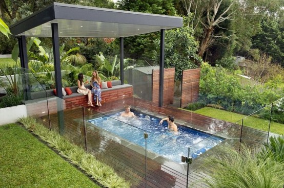a small plunge pool and a deck around plus a glass fence to keep the greenery and pool in order