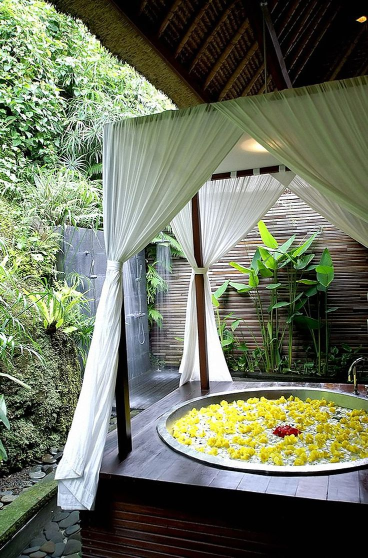 a sunken outdoor bathtub in a wooden platform with curtains for privacy, an outdoor shower and some greenery planted