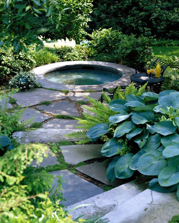 an outdoor bathtub or jacuzzi clad with stones around will be your personal spa and relaxation oasis