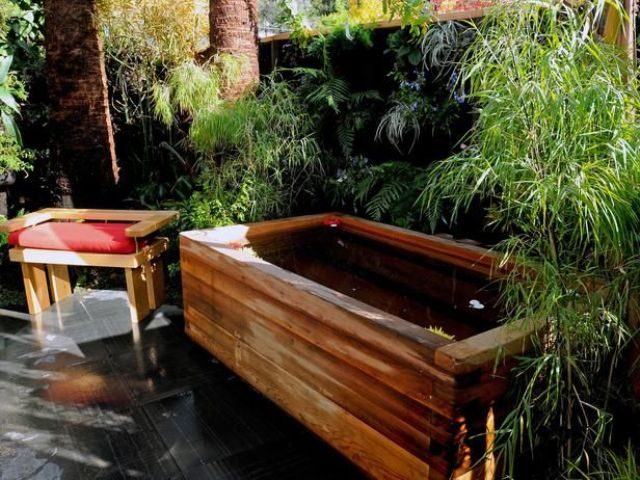 a wooden bathtub placed by a greenery wall plus a simple stool will make up a cool and welcoming outdoor spa