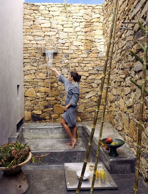 an outdoor waterfall shower with tall stone walls and some greenery and bowls with fruits for a fresh feel
