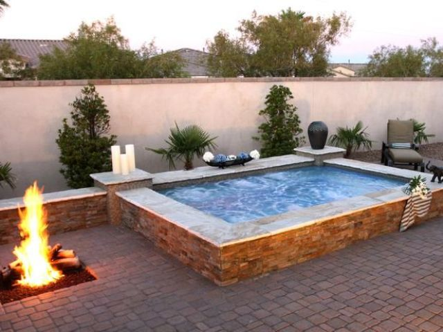 a large outdoor jacuzzi with candles and a fire pit next to it is relaxation with two elements   fire and water