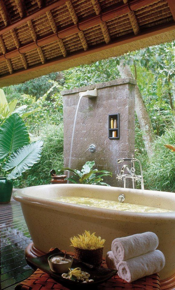 an outdoor waterfall shower and a stone bathtub next to it   you can choose your experience each time you want