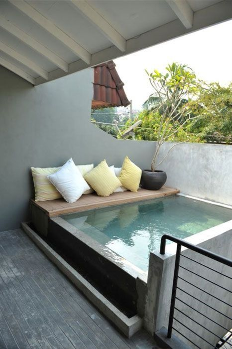 a plunge pool with a tiny deck and pillows on it will fit even the smallest outdoor space