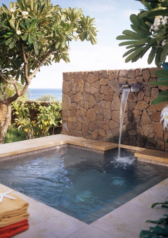 a plunge pool with a waterfall, a stone wall and tiles is a cool idea to relax after a hard and hot day