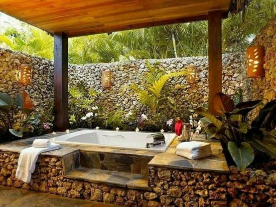 an outdoor bathtub on a stone platform and with stone walls for privacy and potted plants for a fresh and lively feel