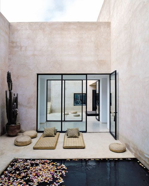 a Moroccan style backyard with loungers, jute ottomans, a plunge pool and a potted cactus