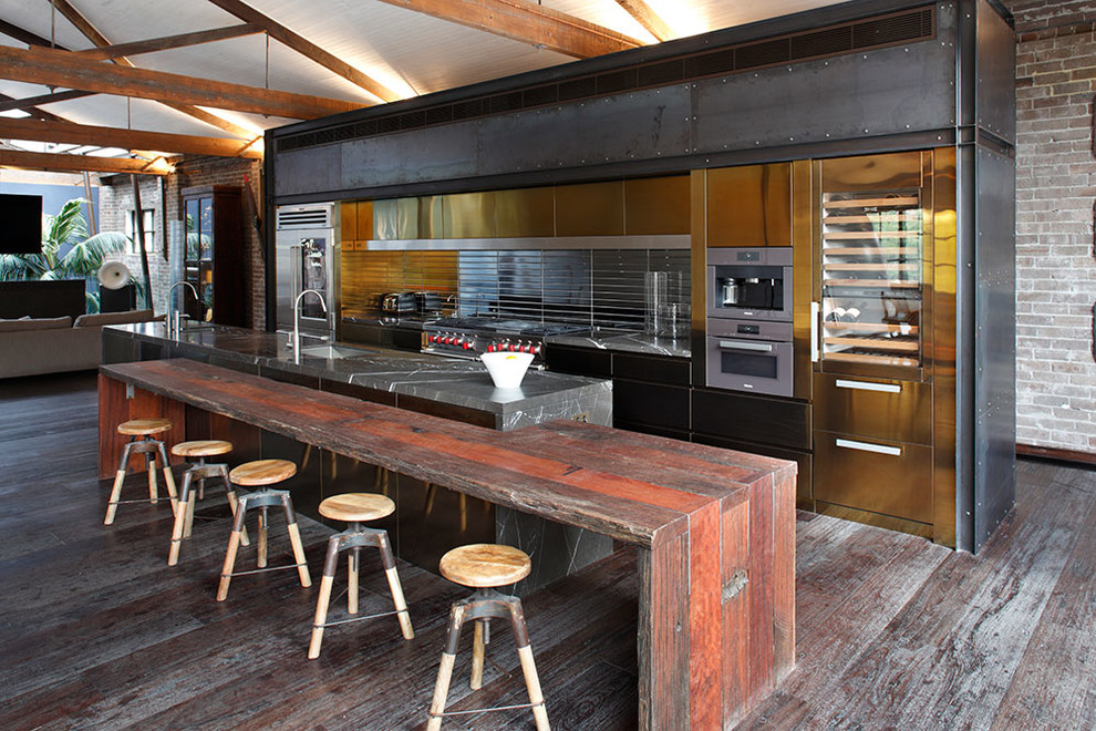 spacious industrial single wall eat in kitchen located in an old factory building with interesting metallic backsplash