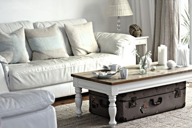 a low shabby chic coffee table with a suitcase under it for storing some things you need