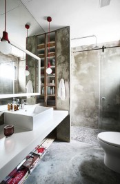 a contemporary industrial bathroom done with concrete, a white vanity with a sink, a shower space, a mirror and touches of red for a bold look