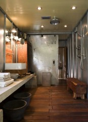a modern industrial bathroom with steel and concrete walls, a wooden floor, a long concrete vanity, stone bowls, a bench is a statement space