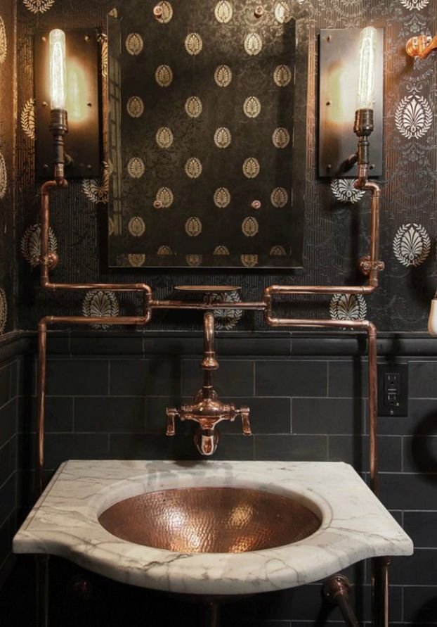 a dark vintage industrial bathroom with black wallpaper walls, black tiles, a stone adn copper sink and copper pipes exposed is a chic space