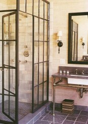 a vintage industrial bathroom with white and grey tiles, a shower space, a sink on a pipe and stone stand and a mirror in a black frame is a chic space