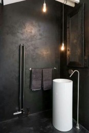 a dark industrial bathroom with metal clad walls, a mirror in a wooden frame, pendant lamps and a free-standing sink