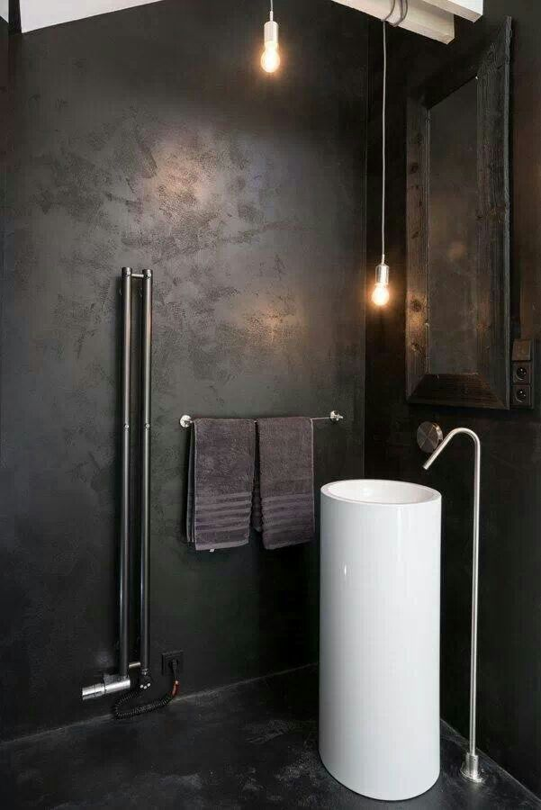 a dark industrial bathroom with metal clad walls, a mirror in a wooden frame, pendant lamps and a free standing sink