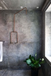 a modern industrial bathroom with concrete walls and a floor, an exposed copper pipe and potted plants is a chic and functional space